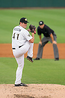 Charlotte Knights starting pitcher Carlos Rodon (41) winds up to deliver a pitch to the plate as third base umpire Drew Maher looks on against the Gwinnett Braves at BB&T Ballpark on August 19, 2014 in Charlotte, North Carolina.  The Braves defeated the Knights 10-5.   (Brian Westerholt/Four Seam Images)