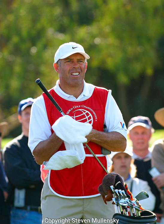 Steve Willaims, Tiger Woods caddy, watches the flight of the ball as he wipes off the club shaft after Woods made a shot.