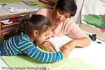 Education preschool 3-4 year olds female teacher scribing writing down description as girl talks about her drawing art activity horizontal