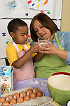 3 year old boy at home with mother, learning to cook looking at level of liquid in measuring cup talking