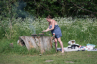 SIDCUP, KENT, ENGLAND - 21 MAY 2020<br /> .<br /> A woman tends to a barbecue while enjoying the hot weather during the current government restricted lockdown of the COVID-19 worldwide pandemic with includes keeping a social distance of 2 metres at Foots Cray Meadow, Sidcup, England on 21 May 2020. Photo by Alan Stanford.