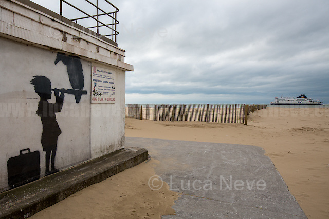 """Banksy: Young girl with a suitcase looking through a telescope with a vulture perched on it staring down near a Calais beach points towards Britain.<br /> <br /> Under the Sky of Calais & Dunkirk. Two Camps, Two Sides of the Same Coin: Not 'migrants', Not 'refugees', just Humans.<br /> <br /> France, 24-30/03/2016. Documenting (and following) Zekra and her experience in the two French camps at the gate of the United Kingdom: Calais' """"Jungle"""" and Dunkirk's """"Grande-Synthe"""". Zekra lives in London but she is originally from Basra in Iraq. Zekra and her family had to flee Kuwait - where they moved for working reason - due to the """"Gulf War"""", and to the Western Countries' will to """"export Democracy in Iraq"""". Zekra is a self-motivated volunteer and founder of """"Happy Ravers"""", a group of people (not a NGO or a charity) linked to each other because of their love for rave parties but also men and women who meet up every week to help homeless people and other people in need in Central London. (Here there are some of the stories I covered about Zekra and """"Happy Ravers"""": http://bit.ly/1XVj1Cg & http://bit.ly/24kcGQz & http://bit.ly/1TY0dPO). Zekra worked as an English teacher in the adult school at Dunkirk's """"Grande-Synthe"""" camp and as a cultural mediator and Arabic translator for two medic teams in Calais' """"Jungle"""". Please read her story at the beginning of this reportage."""