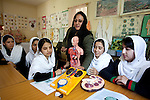 16 June 2013, Qala Wazir, Khoshal Khan, Kabul Province,  Afghanistan.  Teacher Zheela Zohel in a physics and anatomy class with students (from left) Halima Halimi (16),  Asma Monsri (15),  Metra Barakzai (16), Masuda Sarwri (15), and Hena Saadat (16) at Shahid Nahid High School in Kabul.   Much of the funding for the school, including construction, was provided by the Education Quality Improvement Program (EQUIP). The school is benefitting from EQUIP whose objective is to increase access to quality basic education, especially for girls. School grants and teacher training programs are strengthened by support from communities and private providers.  Picture by Graham Crouch/World Bank