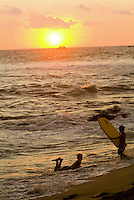 Two boys with body boards play in the surf during sunset at Hano beach, Kona on the Big island of Hawaii.