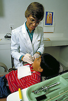 FEMALE DENTAL HYGIENIST WORKING WITH YOUNG PATIENT. DENTAL HYGIENIST. SAN FRANCISCO CALIFORNIA.