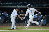 Alex Destino (23) of the Winston-Salem Dash slaps hands with third base coach Ryan Newman (5) after hitting a 2-run home run during the game against the Hickory Crawdads at Truist Stadium on July 10, 2021 in Winston-Salem, North Carolina. (Brian Westerholt/Four Seam Images)