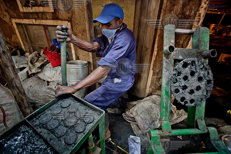 In the Lulana Communal Environmentalist group's backyard workshop, a member shapes briquettes, made from recycled or waste cardboard and used for cooking fuel as an alternative to charcoal or wood, into a cylindrical shape using a machine funded by a European government. The manufacture of briquettes gives off a lot of smoke. Members of the group protect themselves with surgical masks. LCE sells its briquettes to individuals and restaurants.