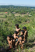 Mato Grosso State, Brazil. Aldeia Metuktire (Kayapo). Kayapo boys with a view of the village, with football goal posts, with the river behind from the top of the hill.