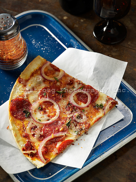 A large slice of pepperoni pizza on a blue tray with a shaker of pepper flakes and napkin. On a wooden table, overhead view.