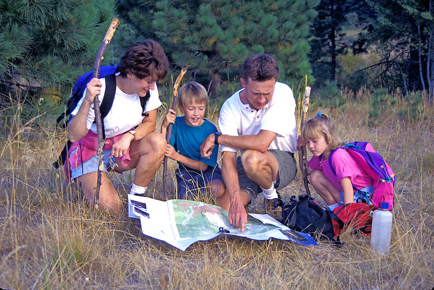 Family hiking and navigating using map and compass, Mt. Shasta, California