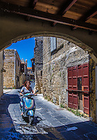 Urban Street Photograph of a lady driving her scooter through the narrow city streets of Rhodes, Greece.