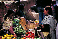 Smiling woman holds scales and gathers string beans for stolid Tibetan woman; both profile; straw baskets; other produce and people; plinth of Maju Deval Temple. Kathmandu, Nepal.