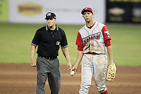 Williamsport Crosscutters first baseman Kelly Dugan #25 tosses the ball back to the pitcher with umpire Robert Moreno looking on during a game against the Batavia Muckdogs at Dwyer Stadium on August 5, 2011 in Batavia, New York.  Williamsport defeated Batavia 5-4.  (Mike Janes/Four Seam Images)