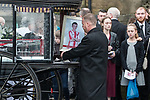 © Joel Goodman - 07973 332324 . 20/12/2017. Manchester, UK. Sam's photo is placed inside the hearse outside the church after the service . The funeral of 14-year-old Sam Berkley at Christ Church in Denton , East Manchester . Mourners wear red and white , the colours of Hattersley FC , for whom Berkley played . Amongst their number are pupils and friends from Audenshaw School . Berkley died after being hit by a grey BMW near junction 3 of the M67 in Hyde , East Manchester , on 1st December 2017 . Photo credit : Joel Goodman