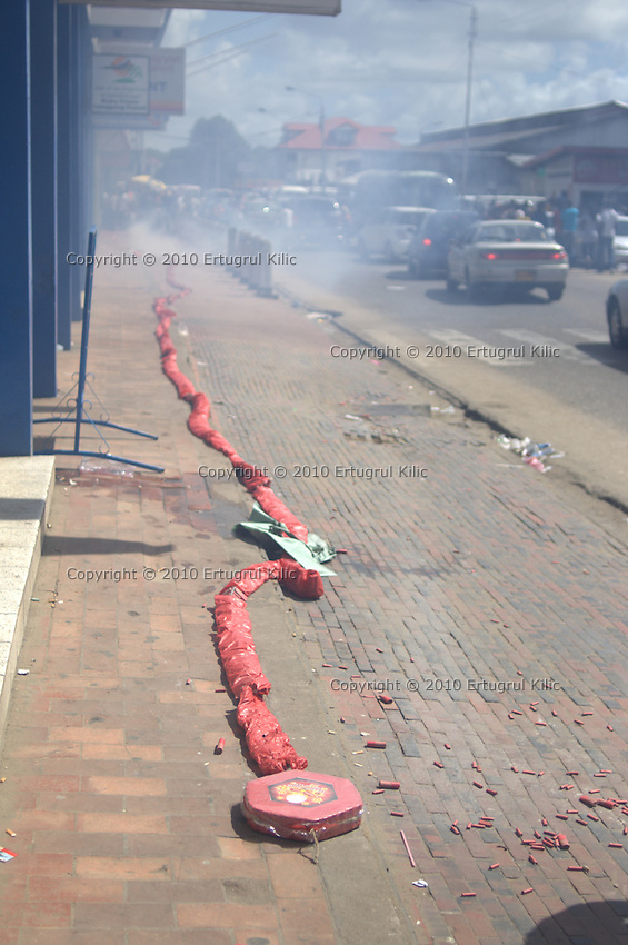 Head (end) part of hundred meters long firecracker lays on the ground. Vehicle traffic flows normally while hundred meters long of firecrackers exposing and laying on the sidewalk of busy street.....End of year 2010 celebrations on the streets of Paramaribo. Suriname is one of biggest consumer in South America that using firecrackers, fireworks ( also locally known as pagara ) for celebrations, especially for end of every years and also beginning of every new Chinese Years.