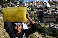 MADAGASCAR Antananarivo, homeless family, woman carry water in jerry can