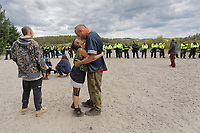 Pictured: A young couple embrace and kiss in front of the police line. Monday 31 August 2020<br /> Re: Around 70 South Wales Police officers executed a dispersal order at the site of an illegal rave party, where they confiscated sound gear used by the organisers in woods near the village of Banwen, in south Wales, UK.