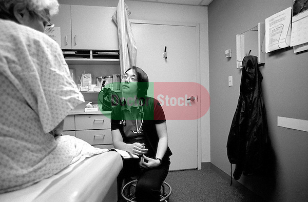 Young female doctor listening to seated elderly female patient in examination room