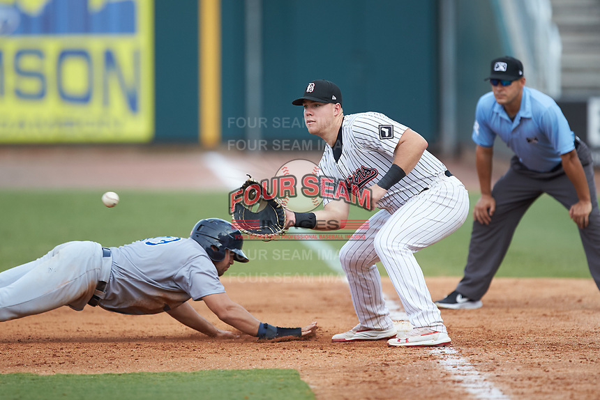 Alex Kirilloff (19) of the Pensacola Blue Wahoos dives back into first base as Gavin Sheets (24) of the Birmingham Barons waits for a pick-off throw at Regions Field on July 7, 2019 in Birmingham, Alabama. The Barons defeated the Blue Wahoos 6-5 in 10 innings. (Brian Westerholt/Four Seam Images)