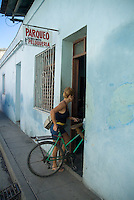 Woman parking her bicycle inside a barbershop, Santa Clara, Villa Clara, Cuba.