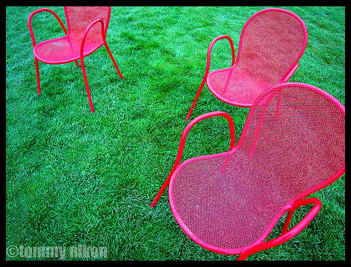 Three bright pink lawn chairs