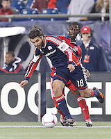 Chicago Fire midfielder Patrick Nyarko (14) almost disrupts attacking New England Revolution substitute midfielder Juan Toja (18). In a Major League Soccer (MLS) match, the New England Revolution (blue) defeated Chicago Fire (red), 1-0, at Gillette Stadium on October 20, 2012.