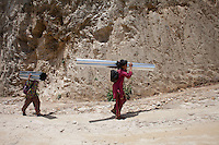 Two children carry materials for their home at Karvrepalanchowk, outskirt of Kathmandu, Nepal. May 1, 2015
