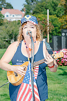"A woman sings the 1960s folk anthem ""Get Together"" by the Youngbloods (""Come on people now, smile on your brother"") as alt-right organization Super Happy Fun America demonstrates against facemasks, vaccines, and pandemic closures, and in support of the reelection of President Donald J. Trump near the residence of Massachusetts governor Charlie Baker in Swampscott, Massachusetts, on Sat., Sept. 26, 2020. Super Happy Fun America is most well known for organizing the Straight Pride Parade in Boston on August 31, 2019."
