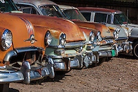 Once gleeming chrome still stands out on a row of rusted antique autos from decades ago, for sale on a small town main street.