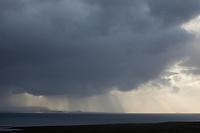 Regen über dem Meer, Unwetter, Wetter, Sonnenstrahlen, Wolkenhimmel, Regenschauer, Schauer, Wolken, Wolke, Regenwolke, Regenwolken, Regenfront, Unwetterfront, Regen unter den dunklen Wolken wird von der Sonne angestrahlt, Nordatlantik, Atlantik, Atlantischer Ozean, Island, Iceland