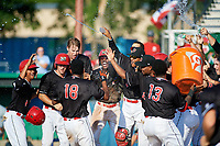 Batavia Muckdogs center fielder Brayan Hernandez (18) is mobbed by teammates after hitting a game winning grand slam home run in the bottom of the ninth inning during a game against the West Virginia Black Bears on July 1, 2018 at Dwyer Stadium in Batavia, New York.  From left, Gerardo Nunez (1), Matt Brooks (15), Sean Reynolds (25), Demetrius Sims (3), Igor Baez (29), Pablo Garcia (4), Elkin Alcara (30), and Albert Guaimaro (13).  Batavia defeated West Virginia 8-4.  (Mike Janes/Four Seam Images)