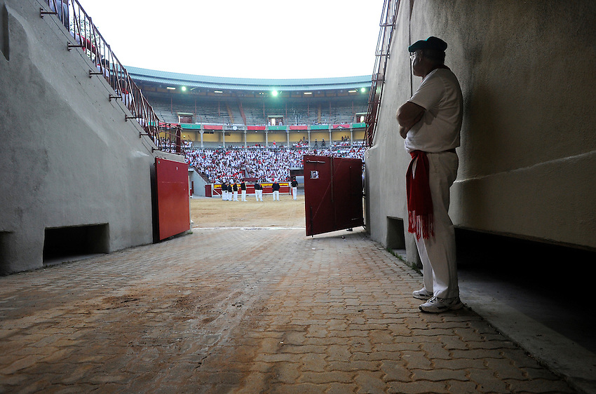 A bullring worker waits the beginning of the fifth San Fermin Festival´s running of the bulls, on July 11, 2013, in Pamplona, Basque Country. On each day of the eight San Fermin festival days six bulls are released at 8:00 a.m. (0600 GMT) to run from their corral through the narrow, cobbled streets of the old navarre town over an 850-meter (yard) course. Ahead of them are the runners, who try to stay close to the bulls without falling over or being gored. (Ander Gillenea / Bostok Photo)
