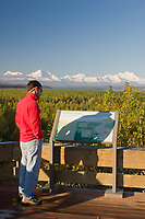 Tourist reads about the Alaska Range at a nature kiosk, Delta Junction, Alaska