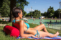 Portrait of a sexy young woman having sunbathing on a beach towel at Deep Eddy Pool on a bright sunny day in Austin, Texas.