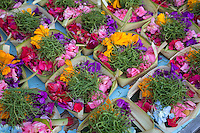 Bali, Indonesia.  Religious offerings (canang) are made by an offerings specialist (tukang banten), to sell to individuals too busy to make their own.  Flower petals and betel are common ingredients.