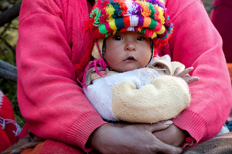 A Peruvian baby sits in its mothers lap wearing a colorful handmade hat made in their local weaving community. zin the weaving village of Huilloc, kids begin to learn how to use the back strap loom at a young age so that they can assist with the weaving and spinning process in their community.