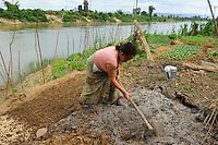 Laos, woman cultivates vegetable field near river, improvement of soil with compost and ash / Laos, Farmerin baut Gemuese an einem Fluss an, Verbesserung des Bodens mit Kompost und Asche