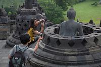 Borobudur, Java, Indonesia.  Tourists Photographing Buddha Statue.