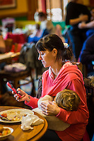 A mother breastfeeds her child while sitting at a table during  a sling meet held in the family restaurant and play area in a pub. She is texting on her mobile phone.<br /> Lancashire, England, UK<br /> <br /> Date Taken:<br /> 07-01-2015<br /> <br /> © Paul Carter / wdiip.co.uk