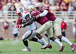 North Carolina State wide receiver Stephen Louis is brought down after a long reception by Florida State defensive backs Levonta Taylor, second from left, and Ermon Lane, right in the second half of an NCAA college football game in Tallahassee, Fla., Saturday, Sept. 23, 2017.  NC State defeated Florida State 27-21. (AP Photo/Mark Wallheiser)