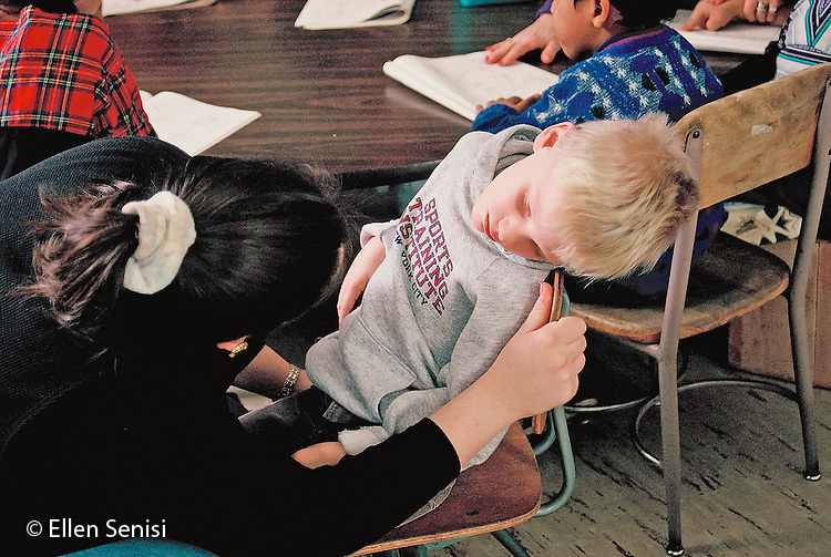 MR / Schenectady, NY.Yates Arts Magnet School / Special Education Class.Aide talks with upset student who will not listen to lesson. (Boy, 5, Multiply Handicapped including ADHD, on Ritalin, Developmentally Delayed, Distractible, Impulsive).MR: Bul1, Edw1.© Ellen B. Senisi