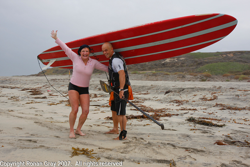 """Tom Jones is greeted by Jericho Poppler after he arrived at the US Mexico border at Border Field State Park, the south-western most corner of the contiguous United States on Friday November 9 2007.  Jones became the first person to paddle the entire 1250-mile coast of the California on a paddleboard when his three and a half month long journey ended at the border fence in southern San Diego.   The expedition, called """"California Paddle 2007? was designed to draw attention to the problem of plastic pollution in the world?s oceans and its detrimental effect on marine life.  (Photo Ronan Gray)"""