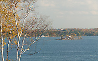 Crossover Island Lighthouse and the distant American shore in late autumn on the St. Lawrence River. Taken from the 1000 Islands Parkway, Southern Ontario.