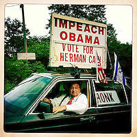 A Herman Cain supporter parks his car and sign along a road near the site of the first New Hampshire debate of the 2012 Presidential campaign in Manchester, New Hampshire.