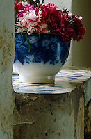 A 19th century blue-and-white faience bowl filled with a cheerful collection of carnations stands on the wide window sill of the garden room