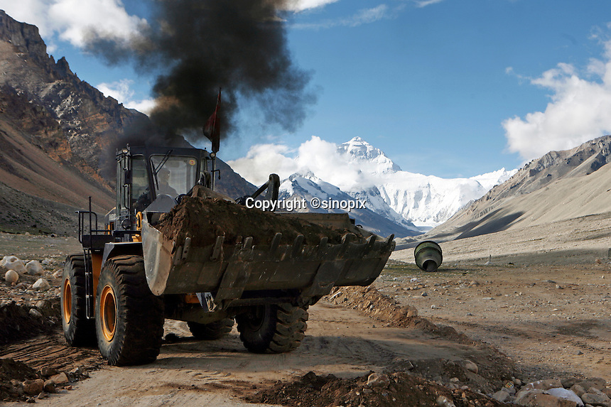 """A bulldozer belches smoke as it clears a road to everest base camp.China started building a controversial 67-mile """"paved highway fenced with undulating guardrails"""" to Mount Qomolangma, known in the west as Mount Everest, to help facilitate next year's Olympic Games torch relay."""