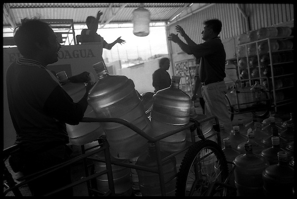 Water delivery men fill their bicycle carts with large water bottles to sell door to door throughout the city. This is the only way that most people get clean water, given that what city water exists is polluted once it reaches the houses through the city's outdated plumbling system.....