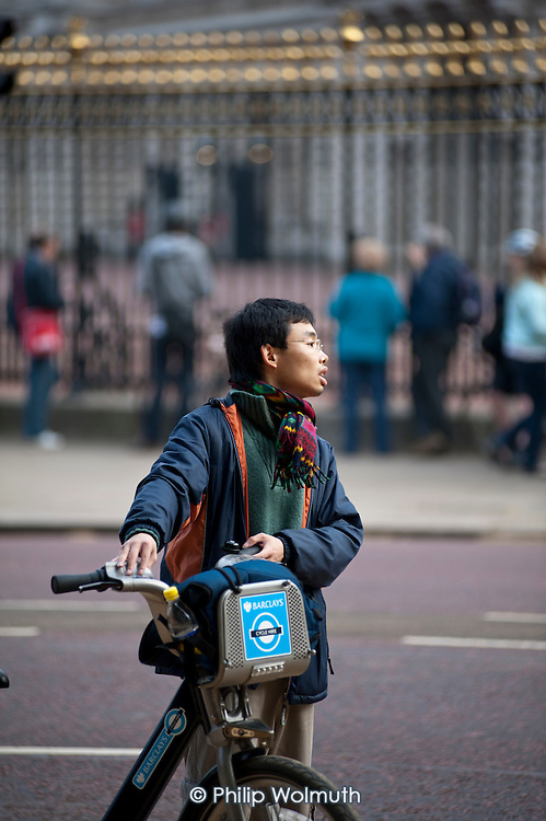 A cyclist outside Buckingham Palace with a bike from the Barclays cycle hire scheme organised by the Greater London Authority.