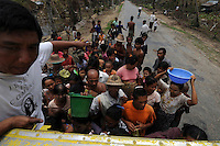 Rice is distributed to a village devastated by Cyclone Nargis, which hit Burma in May 2008. Private donations had been forbidden by the junta, who insisted that all aid must be distributed through them. These people decided to do it anyway. Despite his T-shirt, the man is a Buddhist.