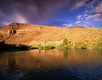 Fly fisherman on Owyhee River at sunset. Near Adrian, Oregon.